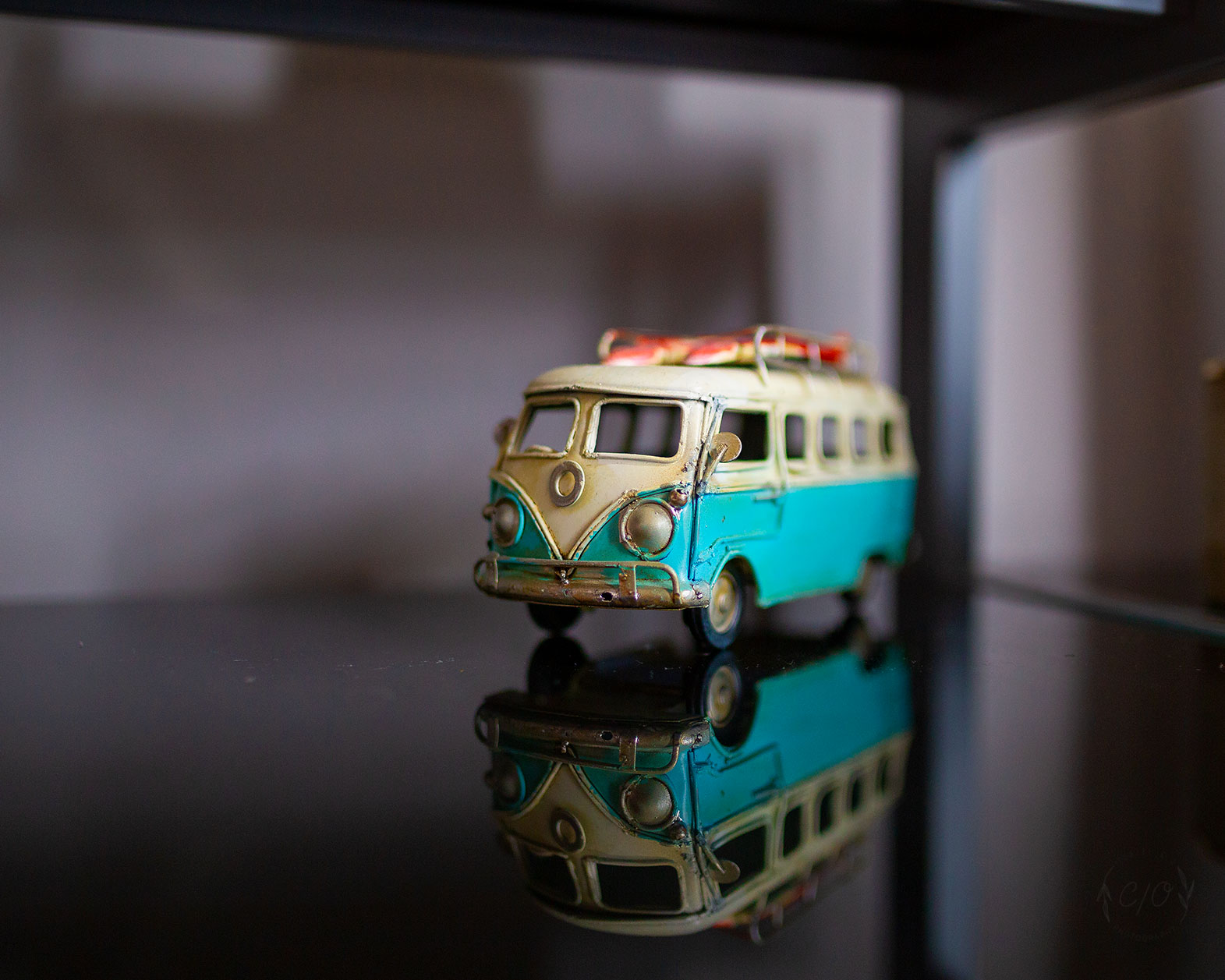 A Photograph of a Toy Kombi on a reflective surface